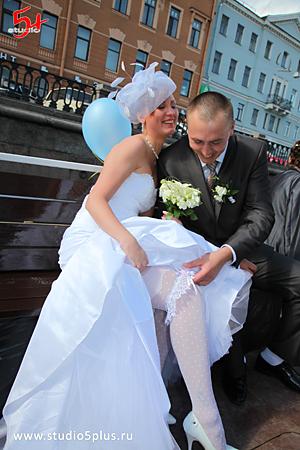 Жених снимает подвязку с ноги невесты